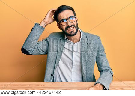 Young hispanic man working at the office confuse and wonder about question. uncertain with doubt, thinking with hand on head. pensive concept.