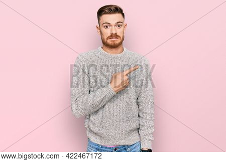Young redhead man wearing casual winter sweater pointing aside worried and nervous with forefinger, concerned and surprised expression