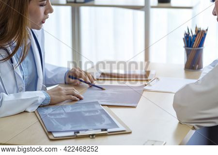 Two Asian Women Doctors Discuss Meeting Doctor's Office Medical Clinic Looking X-ray Film Consulting