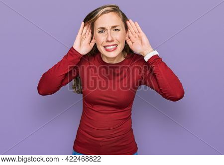 Young blonde woman wearing casual clothes trying to hear both hands on ear gesture, curious for gossip. hearing problem, deaf