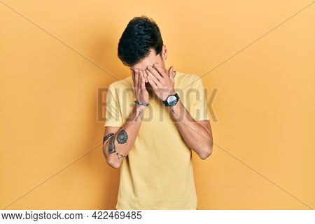 Young hispanic man wearing casual yellow t shirt rubbing eyes for fatigue and headache, sleepy and tired expression. vision problem
