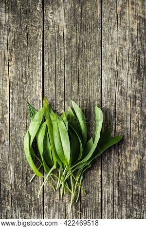 Green ramsons leaves. Wild garlic on old wooden table. Top view.
