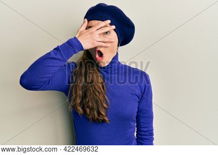 Young blonde woman wearing french look with beret peeking in shock covering face and eyes with hand, looking through fingers afraid