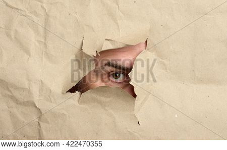 Torn Hole In Brown Paper With Male Peeping Eye, Man Spying And Peeping, Close Up