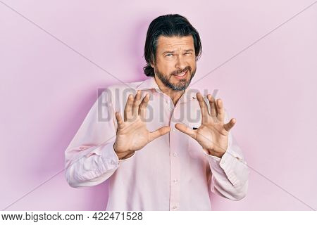 Middle age caucasian man wearing casual clothes disgusted expression, displeased and fearful doing disgust face because aversion reaction. with hands raised
