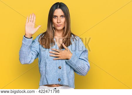 Young woman wearing casual clothes swearing with hand on chest and open palm, making a loyalty promise oath