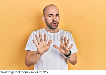 Young bald man wearing casual white t shirt moving away hands palms showing refusal and denial with afraid and disgusting expression. stop and forbidden.