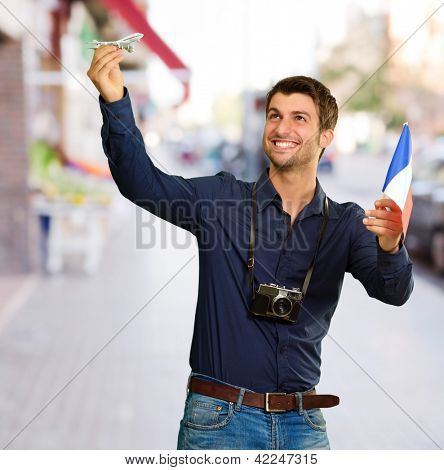Man holding flag and miniature of airplane, outdoor poster