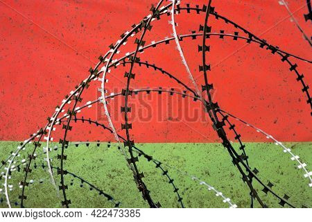 Twisted Barbed Wire On The Background Of The Belarusian Flag. Concept: The Iron Curtain, The Occupat
