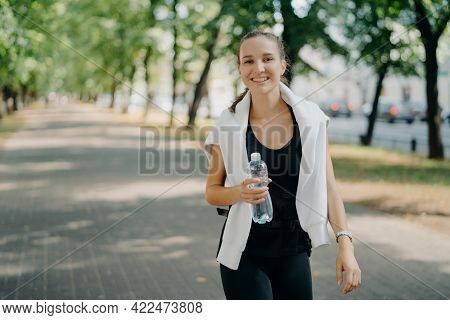 Outdoor Shot Of Glad Sporty Woman Drinks Fresh Water From Bottle Has Walk During Summer Green Urban