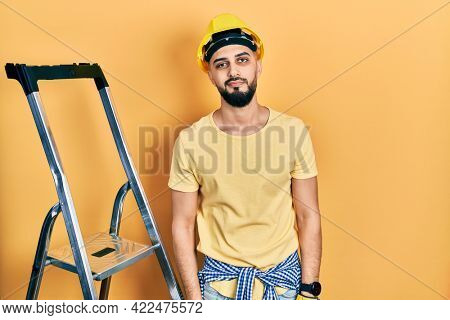 Handsome man with beard by construction stairs wearing hardhat looking sleepy and tired, exhausted for fatigue and hangover, lazy eyes in the morning.