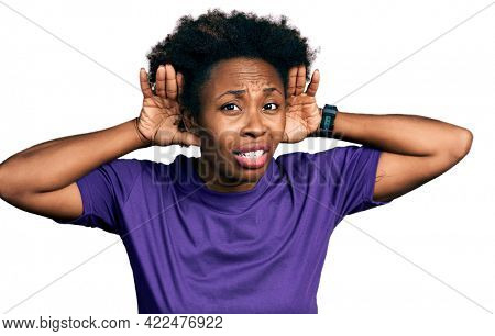 African american woman with afro hair wearing casual purple t shirt trying to hear both hands on ear gesture, curious for gossip. hearing problem, deaf
