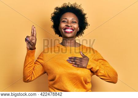 Young african american woman wearing casual clothes smiling swearing with hand on chest and fingers up, making a loyalty promise oath