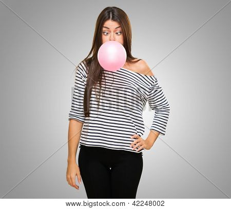 Young Woman Blowing Bubblegum and crossing her eyes against a grey background