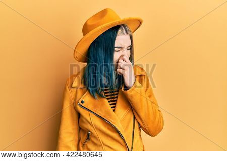 Young modern girl wearing yellow hat and leather jacket smelling something stinky and disgusting, intolerable smell, holding breath with fingers on nose. bad smell