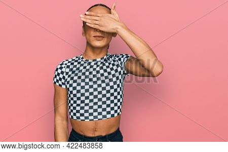 Hispanic transgender man wearing make up and long hair wearing modern clothes smiling and laughing with hand on face covering eyes for surprise. blind concept.