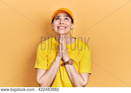 Young hispanic woman wearing delivery uniform and cap begging and praying with hands together with hope expression on face very emotional and worried. begging.