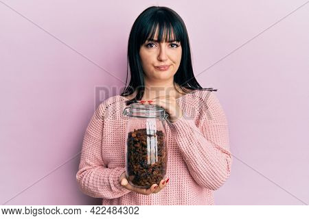 Young hispanic woman holding jar of raisins skeptic and nervous, frowning upset because of problem. negative person.