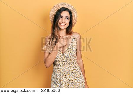 Young hispanic girl wearing summer hat cheerful with a smile of face pointing with hand and finger up to the side with happy and natural expression on face