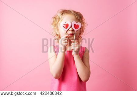 Little Girl Holding Large Heart-shaped Lollipops In Her Hands On A Pink Background.