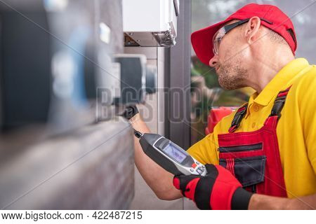 Caucasian Technician In His 40s With Gas Leak Detector Performing Scheduled Check And Heating Furnac