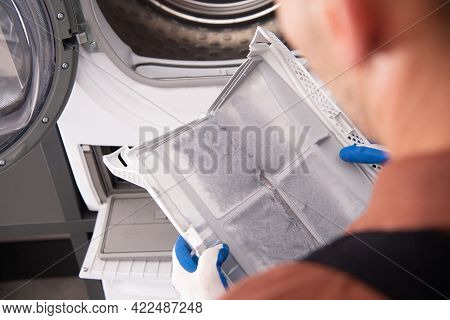 Washing And Dryer Machine Filter Covered By Dirt. Filter Cleaning Performed By Home Appliances Techn