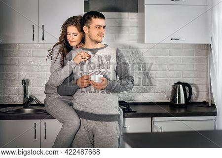 Young Man And Woman Are Drinking Hot Coffee Or Tea And Hugging In The Kitchen. A Young Family Has Br