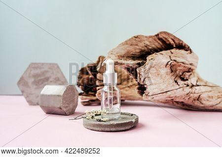Front View Of Face Serum Bottle. Concrete.