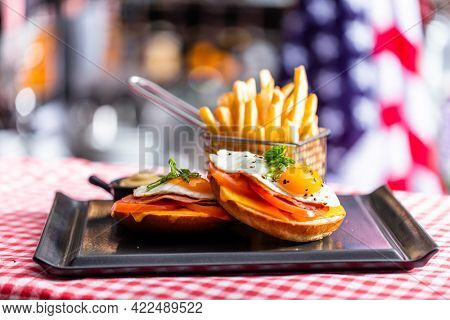 Sandwich with fried egg and french fries breakfast served in american restaurant