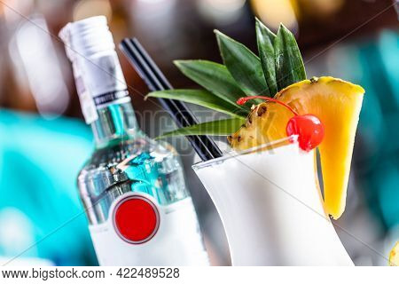 Pina colada coctail on bar counter with fresh pineapple and alcohol bottle.