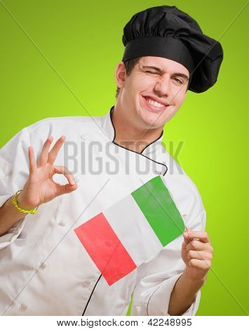 Portrait Of A Young Chef Holding Italian Flag And Winking against a green background