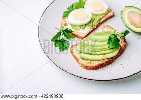 Toast With Avocado And Egg On White Plate. Top View. Healthy Breakfast