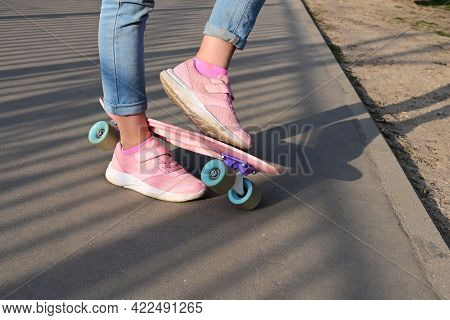 Close-up Legs Of  Girl Skateboarder In Blue Jeans And Pink Sneakers, Riding  Pink Penny Skate Longbo
