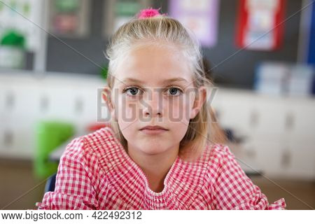 Portrait of caucasian girl sitting on her desk in the class at school. school and education concept