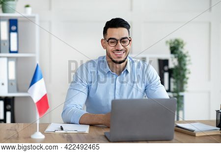 Online Foreign Languages Tutoring. Cheerful Arab Male Teacher Giving French Class, Communicating On