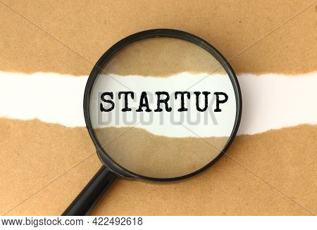 The Magnifying Glass Reveals The Startup Text Appearing Behind The Torn Brown Paper. Business Concep