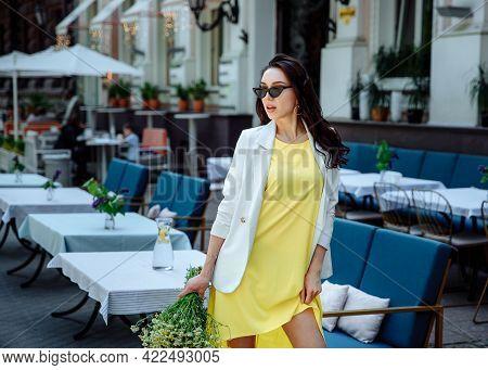 Fashion Portrait Stylish Urban Girl With Flowers Posing Old City Street. Close-up Fashion Woman Posi