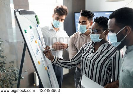 Black Manager In Medical Mask Presenting Business Strategy On Whiteboard