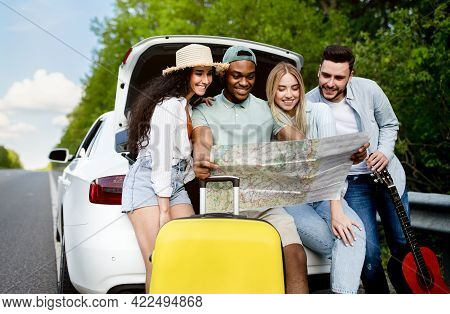 Traveling With Friends. Happy Multiracial Young People Sitting In Open Car Trunk, Checking Map, Havi
