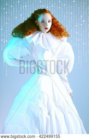 Fashion art history. Sophisticated female model with lush red curly hair posing in a white art dress with late renaissance ruffled collar. Studio portrait.