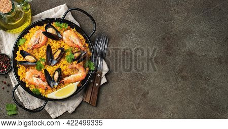 Traditional Spanish Seafood Paella In Pan With Chickpeas, Shrimps, Mussels, Squid On Brown Concrete