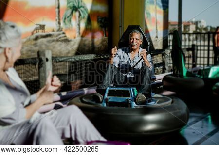 Senior couple on a bumper car ride in an amusement park