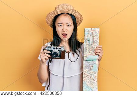 Young chinese girl holding city map and vintage camera in shock face, looking skeptical and sarcastic, surprised with open mouth