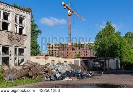 Construction Crane On A Background Of Blue Sky And Dilapidated Old Buildings With A Landfill And Rub