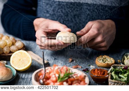 closeup of a young caucasian man cutting a bread bun to prepare a mini sandwich or some vegan appetizers, sitting at a gray wooden table, next to a bowl with a tomato salad and other vegan ingredients