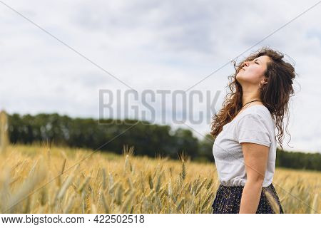 Young Carefree Woman In Rustic Dress Breathing Deep Fresh Air In A Grassy Field. Space For Text. Wal