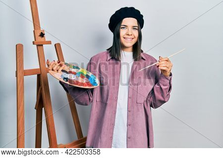 Young brunette woman standing by empty easel stand holding palette smiling with a happy and cool smile on face. showing teeth.