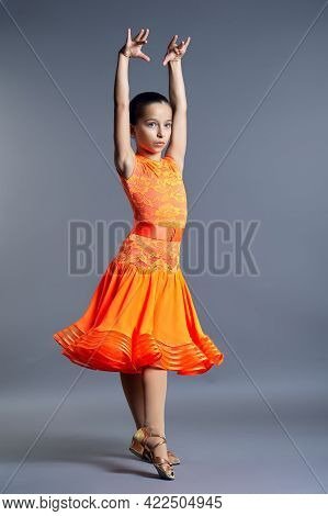 Child Girl In An Orange Sports Dress Posing In Dance Movement On Gray Background