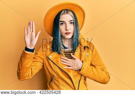 Young modern girl wearing yellow hat and leather jacket swearing with hand on chest and open palm, making a loyalty promise oath