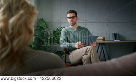 A young professional psychotherapist explaining to a patient the causes of depression